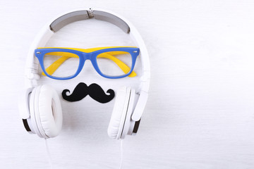 Glasses, mustache and headphone forming man face