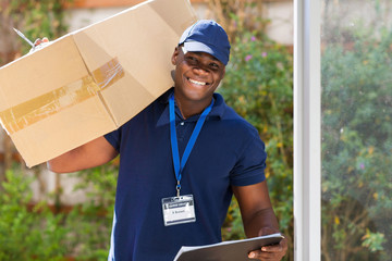 african courier standing with parcel at the door