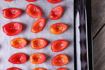 Tomatoes on drying tray, on wooden background