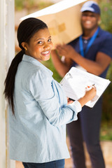 black woman signing document for receiving package