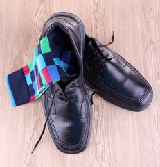 Black man's shoes and pair of socks on wooden background