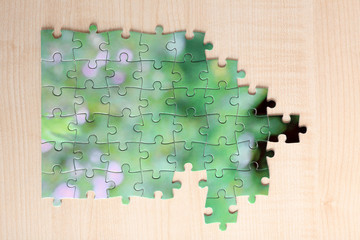 Puzzles with beautiful landscape on wooden background