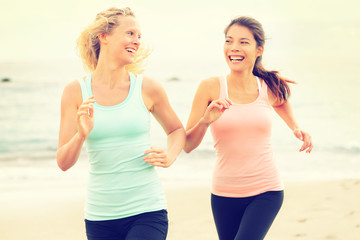 Women running exercising jogging happy on beach