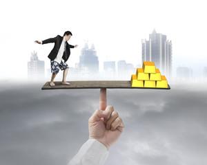 businessman stands on finger seesaw vs gold