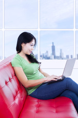Beautiful woman working with laptop on red sofa