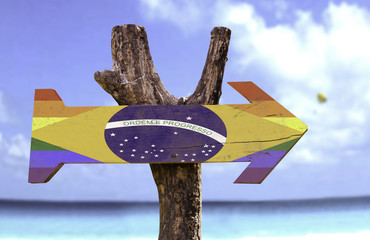 Brazil Gay Flag wooden sign with a beach on background