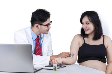 Doctor checking blood pressure of pregnant woman