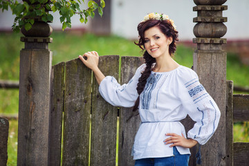 Young beautiful woman in Ukrainian style clothing outdoors
