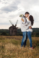 Young couple in Ukrainian style clothes against wooden windmill