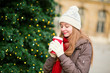 Girl drinking coffee near Christmas tree