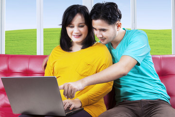 Pregnant female and husband with laptop