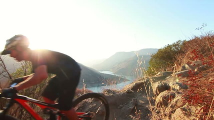 Slow Motion Extreme Mountain Biker Riding Down Hill At Sunset