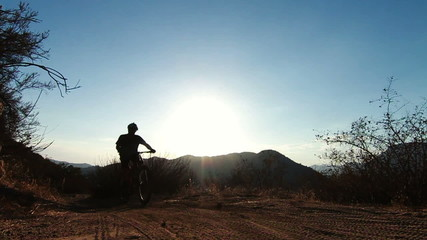 Slow Motion Silhouette of Man Mountain Biking At Sunset