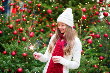 Girl with a sparkler near brightly Christmas tree