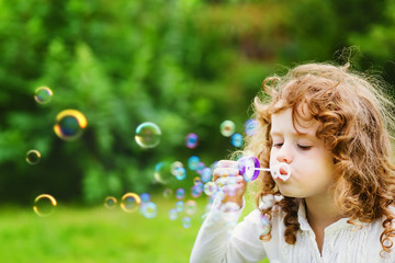 A little girl blowing soap bubbles, closeup portrait beautiful c
