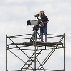 Cameraman working on steel scaffolding.