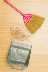 Dirty alopecia hair on laminate floor with broom and dustpan.
