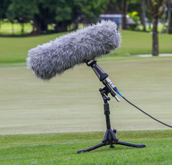 A large microphone boom with stand for TV or Radio situated.