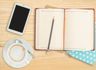 notebook with pencil, smart phone and coffee cup on wooden backg