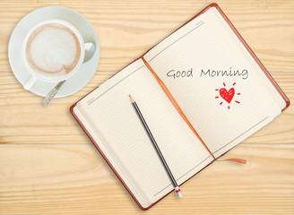 """Good morning"" on notebook with pencil and coffee cup on wooden"