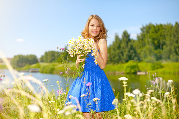 Beautiful girl with bunch of camomiles