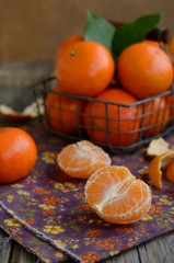 Cloves of tangerines and wire basket full of ripe fruits