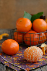 Ripe tangerine fruit and wire basket full of mandarines