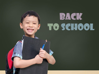"""Young Asian student smiling in front of chalkboard with text """"Ba"""
