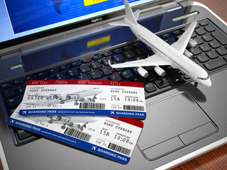 Online ticket booking. Airplane and boarding pass on laptop keyb