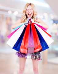 Happy blonde woman with colored shopping bags.