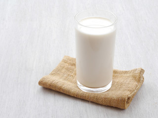 Glass of milk on white wooden floor
