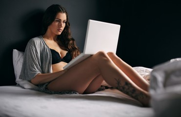 Pretty young woman working on a laptop in bedroom