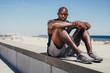 Fit young athlete relaxing on sea wall after workout