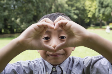 Boy forming heart by his hands