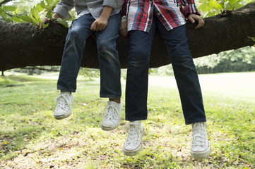 young children's legs relaxing on tree