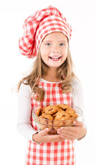 Smiling cute little girl in chef hat holding bowl with cookies
