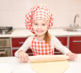 Happy little girl with chef hat rolling dough