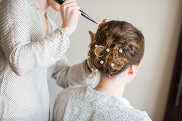 Bride getting her hair done before wedding