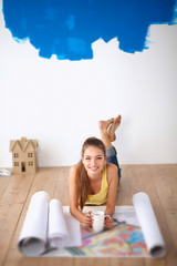 Young woman lying on the floor and looking at blueprint of new