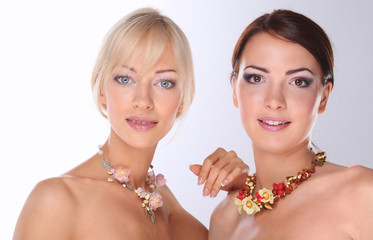 Portrait of a two beautiful women with necklace, isolated on