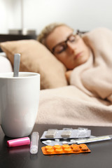 sick woman sleeping in bed, focus on pills