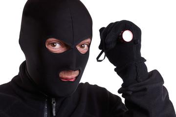maskierter Einbrecher mit Taschenlampe