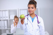 canvas print picture - Female doctor hand holding a green apple, standing in office