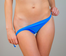 Woman takes off her blue panties.