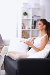 Portrait of young woman watching TV at home sittin on sofa