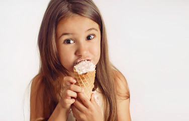 little cute girl having fun with creamy puff on white background