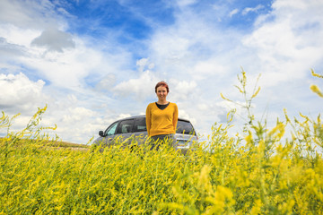 Happy woman with car among canola field
