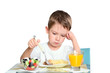 sad little boy sits at the dining table and looking in the plate
