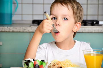 boy eating with a fork at the table