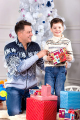 boy with Christmas gift,family in  festive costume near the Chri